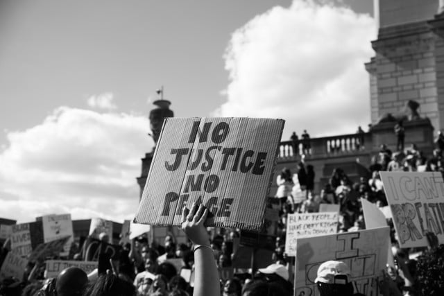 Black and white photo of signs displaying No Justice, No Peace