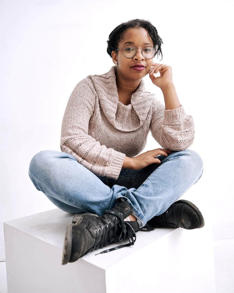 Cheryll Case sitting cross-legged, looking into the camera. Urban Planner of Black Futures on Eglinton.