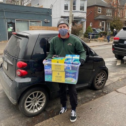 Hanlon holding a container or menstrual products in front of his car