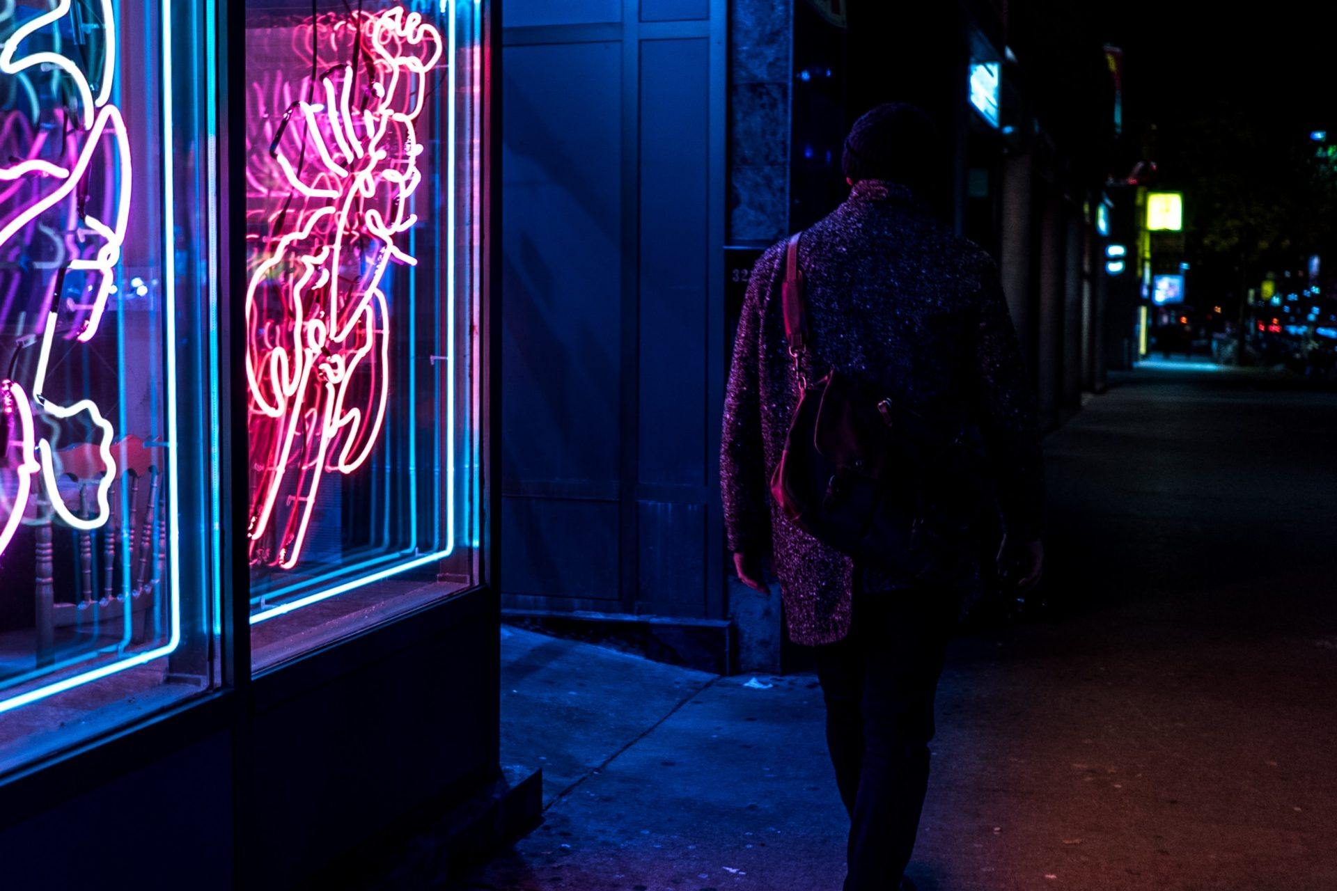 photo of person outside a dimly lit bar at night