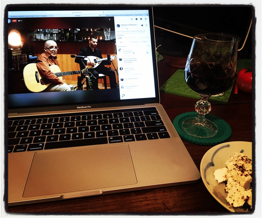 A laptop showing two musicians performing on Facebook Live sits next to food and drink due to COVID-19.