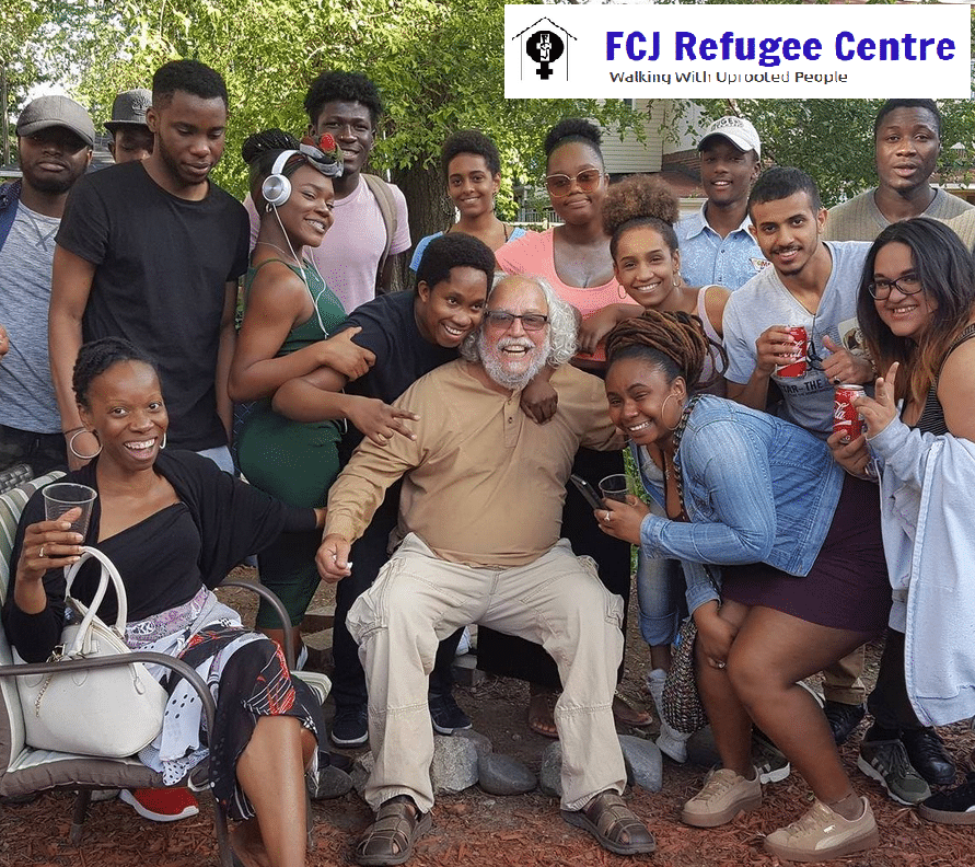 FCG Refugee Centre co-director Francisco Rico Martinez surrounded by community members, smiling into camera