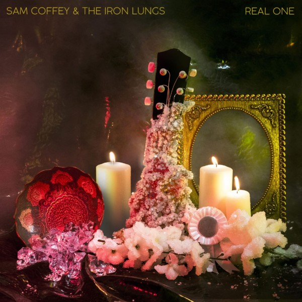 Cover for Sam Coffey and the Iron Lungs album 'Real One'. A guitar neck encrusted with diamonds surrounded by flowers and candles. Dimly lit.