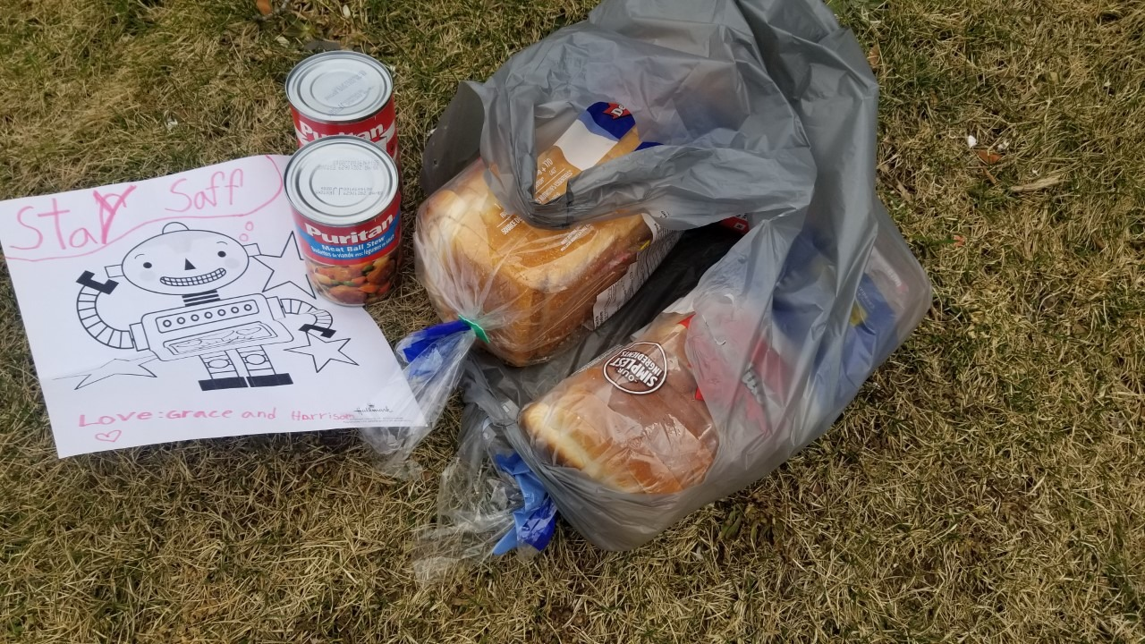 "photo of typical grocery delivery with two loaves of bread and two cans of food. Delivery also includes a handwritten note by a child that reads, ""stay saff'"
