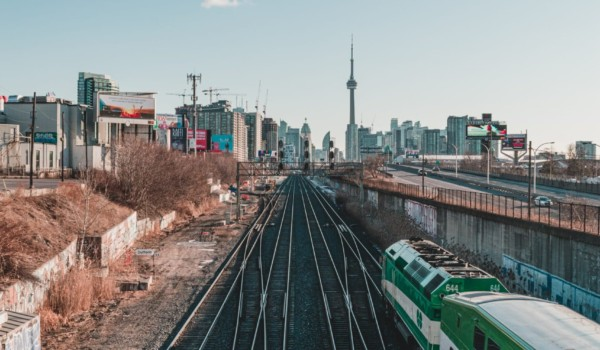 Metrolinx's GO train tracks with GO train in the foreground and CN tower in the background