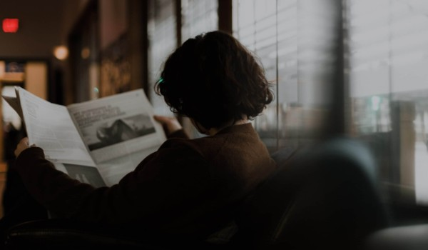woman sitting on couch and reading the newspaper with her back facing us.
