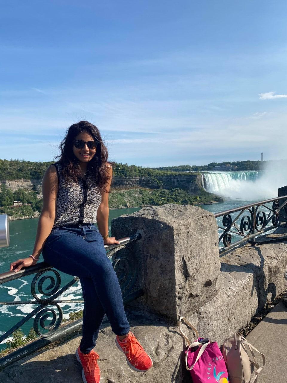 Permanent resident Marushka Loshki Nair sitting on the Niagara Falls railing.