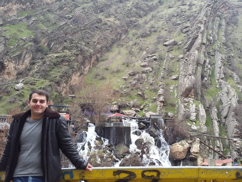 photo of Ehsan leaning against a railing with a mountainous background.