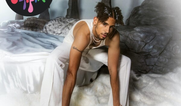 NoMBe sitting in a bed of white sheets while wearing all white.