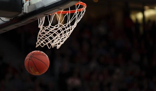 A basketball going through the mesh of a hoop.