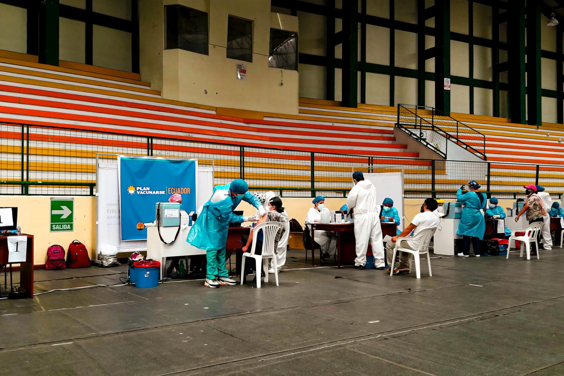 A roll of people sitting down in an arena to receive a needle from a nurse