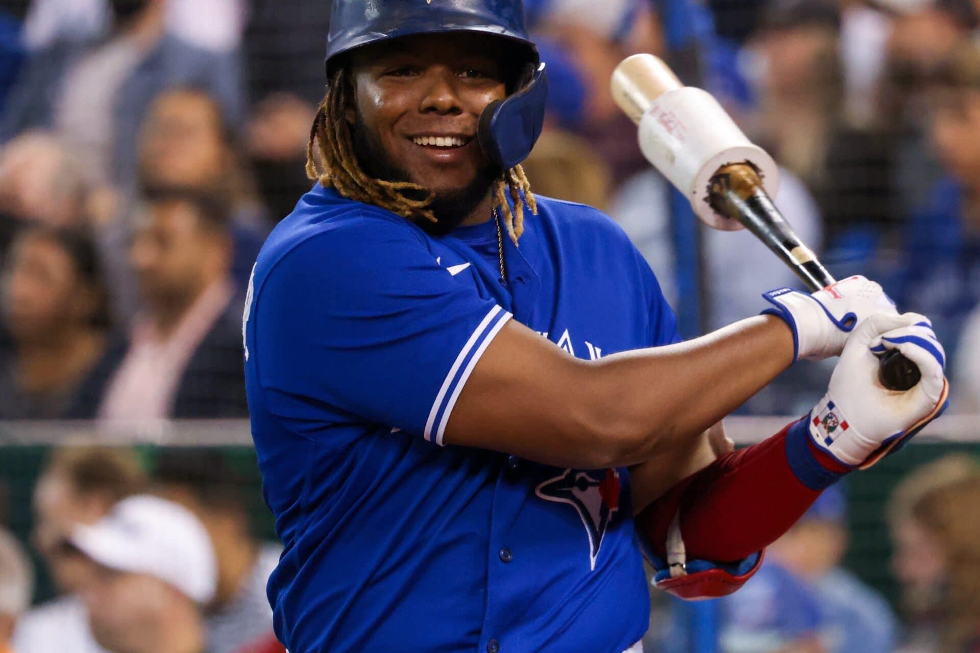 A man in a blue baseball uniform swinging a bat.