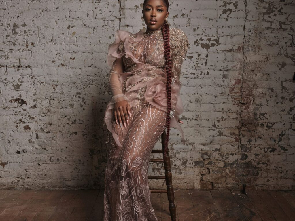 Leila Dey wearing a milk chocolate coloured dress sits on a stool infront of a white brick wall